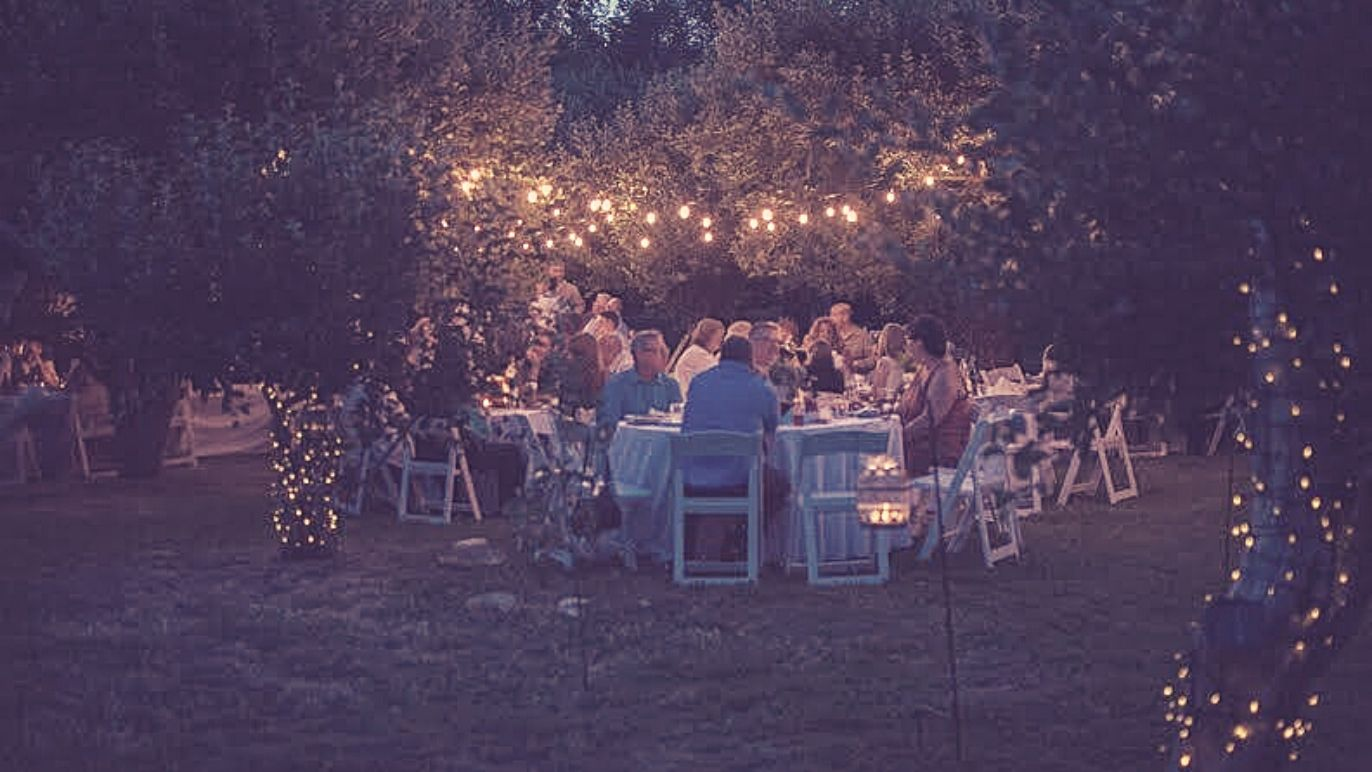 outdoor evening event with lights and white tables with white chairs